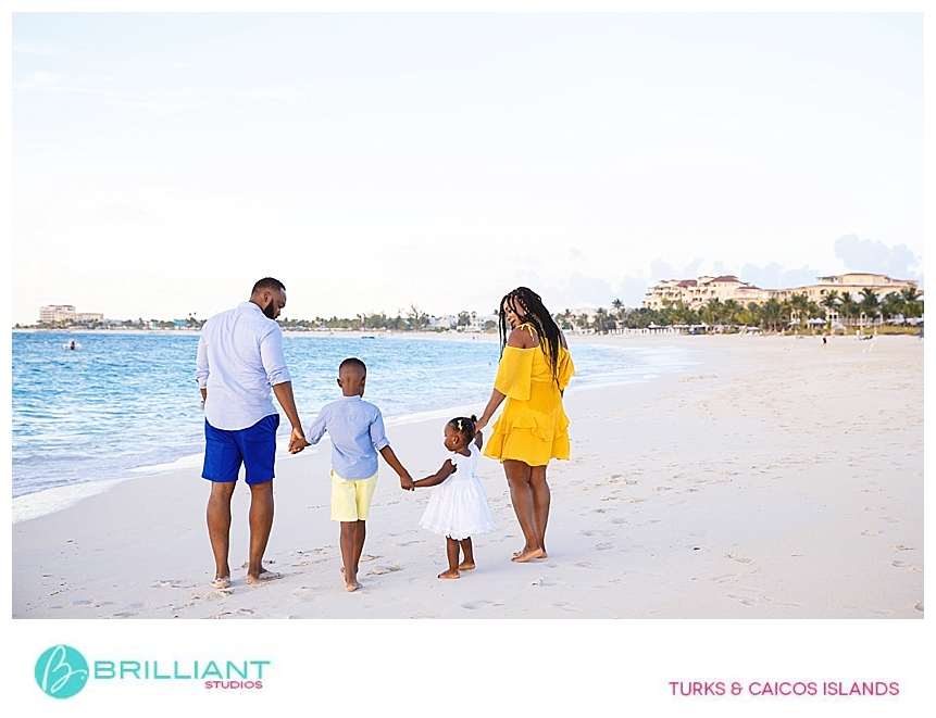family walking on grace bay beach while taking photos